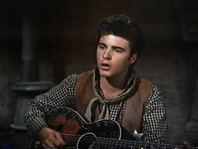 Ricky Nelson plays the guitar and sings backup